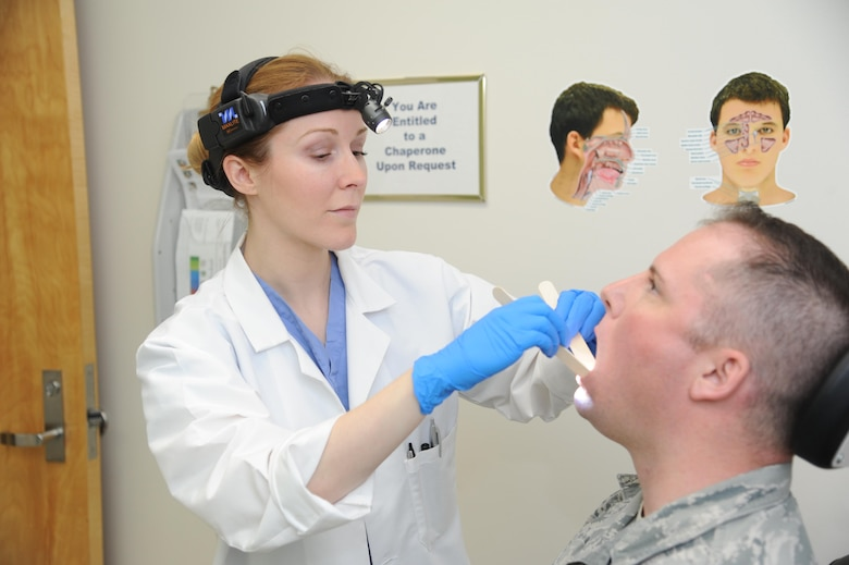 U.S. Air Force doctor (Maj.) Whitney Pafford, Chief, Head and Neck Surgery at Wright-Patterson Medical Center's Department of Otolaryngology, checks a patient for irregularities or signs of cancer. The ENT clinic is hosting a walk-in head and neck cancer screening April 20, 2017 from 9 to 4. The screening for Active-duty military and Tricare beneficiaries will include an exam and information on different types of cancer and their symptoms. (U.S. Air Force photo/Tech Sgt. Scott Johnson)