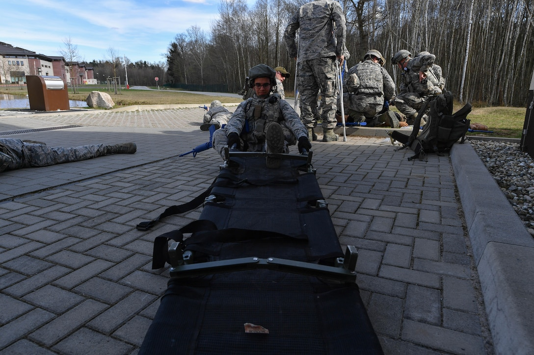 Senior Airman Nigel Crudgington, 100th Security Forces Squadron armor technician, sets up a litter to transport a simulated injured Airman during the tactical combat casualty care portion of the 435th Security Forces Squadron's Ground Combat Readiness Training Center's Security Operations Course on Ramstein Air Base, Germany, March 30, 2017. Airmen assigned to the 86th SFS, 422nd SFS, 100th SFS, and 569th U.S. Forces Police Squadron participated in the course. (U.S. Air Force photo by Senior Airman Tryphena Mayhugh)