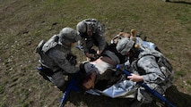 Students of the 435th Security Forces Squadron's Ground Combat Readiness Training Center's Security Operations Course give aid to a simulated injured Airman during the tactical combat casualty care portion of the course on Ramstein Air Base, Germany, March 30, 2017. The students provided medical care, called for a medical evacuation, moved the dummy onto a litter, and carried it to a simulated helicopter while an instructor monitored their actions. Airmen assigned to the 86th SFS, 422nd SFS, 100th SFS, and 569th U.S. Forces Police Squadron participated in the course. (U.S. Air Force photo by Senior Airman Tryphena Mayhugh)