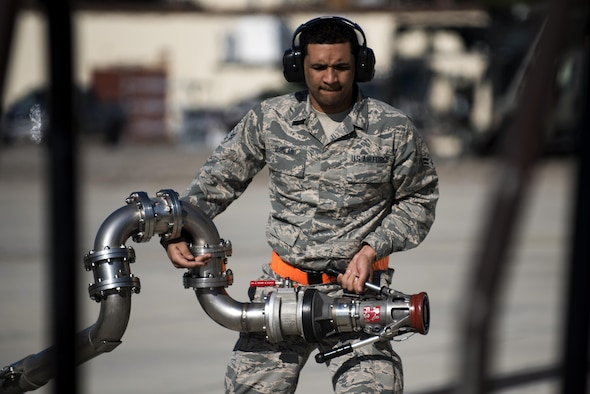 """U.S. Air Force Airman 1st Class Braxton Quinlan, 52nd Logistics Readiness Squadron fuels distributor operator, carries a fuel hose after fueling an F-16 Fighting Falcon at Spangdahlem Air Base, Germany, March 28, 2017. """"Hot pits"""" are a more efficient refueling method because the aircraft is refueled with its engines on, making the refill approximately 30% faster. (U.S. Air Force photo by Airman 1st Class Preston Cherry)"""