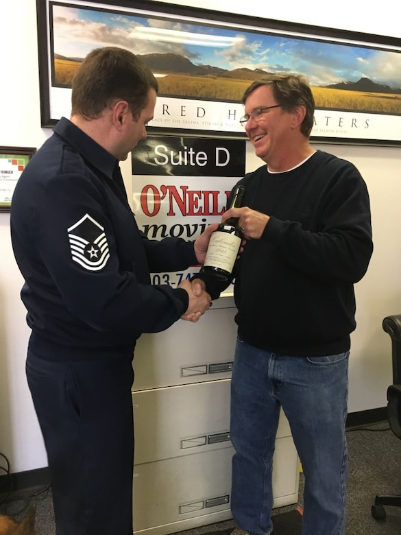Mr. Brad Boland (right), President O-Neill Transfer and Storage Co., hands off a bottle of 1945 Calvados brandy to Master Sgt. Todd Wivell, 62nd Airlift Wing chief of public affairs, March 5, 2017 at the O-Neill business office in Beaverton, Oregon. Boland, along with other members from the east coast to the west coast, assisted in transporting two separate bottles of this brandy in order to help two World War II veterans complete a pact to toast their fallen comrades. (Courtesy photo