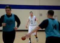 U.S. Air Force Capt. David Cisek, 97th Air Mobility Wing area defense council, dribbles a ball across the court during the championship game, April 4, 2017, at Altus Air Force Base, Oklahoma. The Fitness Center offers several sports throughout the year as a way to support Airmen morale and comradery. (U.S. Air Force Photo by Airman 1st Class Jackson N. Haddon/Released).