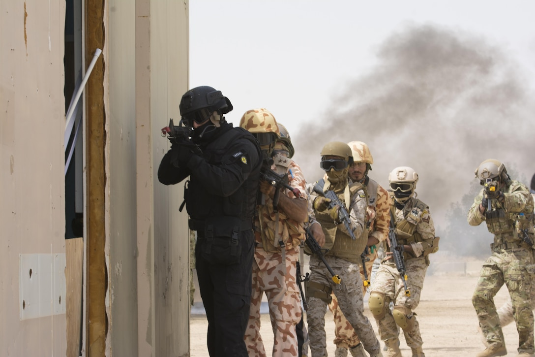 Kuwait- A large crowd of foreign and U.S. dignitaries view teams from their combined special forces- Qatar, Kuwait, Saudi Arabia and the United States, prepare to clear a building and subdue combatants during an explosive training mission proving the successful interoperability of both land and air assets as well as highlighting the vast skills of the varied partner nations part of Operation Eagle Resolve, April 2. 
