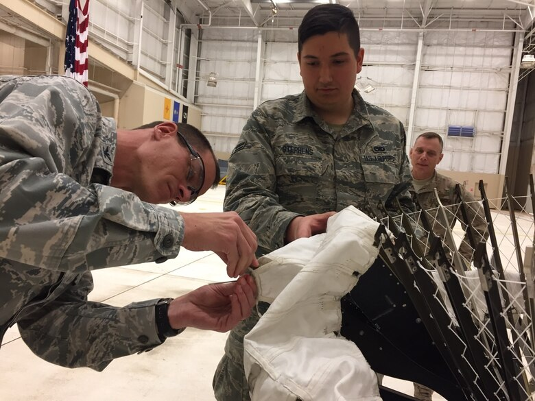 Airman 1st Class Kyle Stephens, hydraulics journeyman with the evaluation team, guides Col. Ben Maitre (left), the base commander, through a repair process on a Variable Speed Drogue assembly, March 7, 2017. Cannon Air Force Base has been the leading edge in testing the VSD, which provides a gap-filler capability to refuel aircraft between low and high speeds; enabling more flexibility for mission support. (U.S. Air Force photo by Tech. Sgt. Manuel J. Martinez)