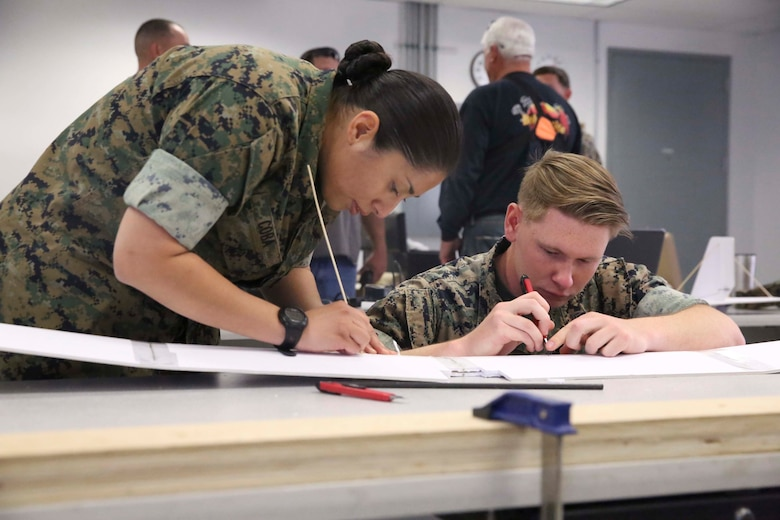 Petty Officer 2nd Class Leyla Coba, cryptologic technician technical, and Cpl. Dylan Lemaistre, signals intelligence and electronic warfare, Tactical Training Exercise Control Group, carve out the wing of a drone at the Fabrication Laboratory aboard Marine Corps Air Ground Combat Center, Twentynine Palms, Calif., March 29, 2017. The newly established FabLab is the first of its kind in the Marine Corps and will provide Marines and sailors the opportunity to develop avant-garde solutions to common problems through utilizing 3D printing technology. (U.S. Marine Corps photo by Cpl. Medina Ayala-Lo)