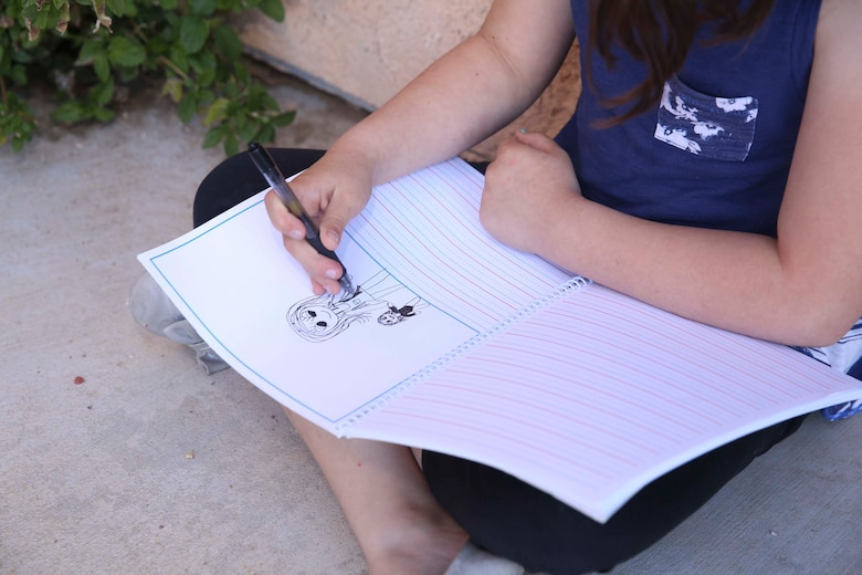 Aubrey Rudd, 7 years old, daughter of Jessica Rudd, Armed Forces Insurance Marine Spouse of the Year 2017 presented by Military Spouse Magazine, draws a photo of herself and her younger sister, Molly, 10 months old, at their home in Yucca Valley, Calif., March 29, 2017, Jessica, a Marine veteran, wife and mother of three, was chosen as the 2017 MSOY for her dedication to helping improve the quality of life of military members and their spouses. (U.S. Marine Corps photo by Cpl. Medina Ayala-Lo)