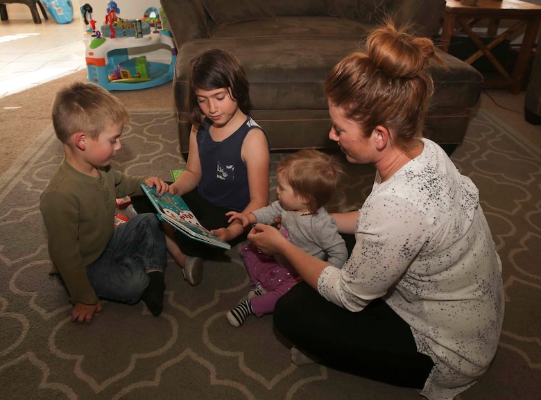 Jessica Rudd, Armed Forces Insurance Marine Spouse of the Year 2017 presented by Military Spouse Magazine, reads a book with her children at their home in Yucca Valley, Calif., March 29, 2017. Rudd, a Marine veteran, wife and mother of three, was chosen as the 2017 MSOY for her dedication to helping improve the quality of life of military members and their spouses. (U.S. Marine Corps photo by Cpl. Medina Ayala-Lo)