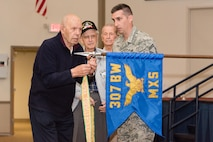Members of the 307th Bomb Wing alumni groups attached streamers to the 307th Maintenance Squadron's guidon representing awards received during World War II, the Korean War, Vietnam and the Cold War during the 75th Anniversary Celebration.