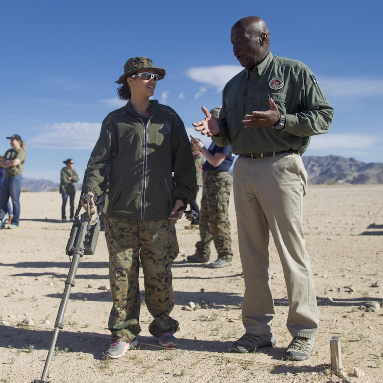 Melvin Harris, counter Improvised Explosive Device instructor, Marine Corps Engineer School, teaches Annie Smack, wife of Gunnery Sgt. Eric Smack, 3rd Battalion, 11th Marine Regiment, how to sweep for IEDs at Range 800 aboard Marine Corps Air Ground Combat Center, Twentynine Palms, Calif., March 30, 2017. (U.S. Marine Corps photo by Cpl. Connor Hancock)