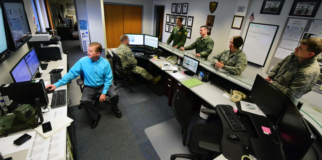Walter Otto, a meteorological technician assigned to the 509th Operations Support Squadron, relays operational data to an aircrew while flight leadership listens in during a brief at Whiteman Air Force Base, Mo., March 29, 2017. Otto earned the title as Air Force Global Strike Command's Weather Civilian of the Year for 2016. (U.S. Air Force photo by Airman 1st Class Jazmin Smith)