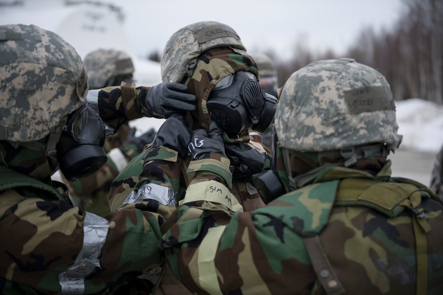 U.S. Air Force Airmen from the 354th Fighter Wing, perform a buddy check on a fellow Airman's gas mask during chemical warfare training for exercise Arctic Gold 17-5 April 6, 2017, at Spruce Lake on Eielson Air Force Base, Alaska. The Airmen were putting on their gas masks in response to a simulated possible chemical threat. (U.S. Air Force photo by Airman 1st Class Isaac Johnson)