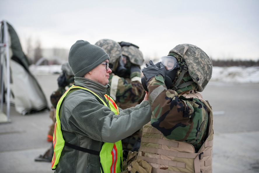 U.S. Air Force Senior Airman Stefanie Nakoneczny-Wood, a 354th Civil Engineer Squadron emergency management journeyman, inspects an Airman's mission-oriented protective posture gear during exercise Arctic Gold 17-5 April 6, 2017, at Spruce Lake on Eielson Air Force Base, Alaska. During this portion of the training, Airmen had to get into full gear anytime they heard the siren go off. (U.S. Air Force photo by Airman 1st Class Isaac Johnson)