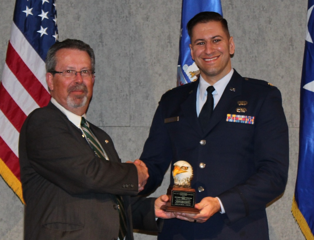 Maj. Nicholas Jamroz, deputy branch chief of the Space Based Infrared Systems Geosynchronous Earth Orbit Satellite office, accepts the AFA 2017 Brent Scowcroft Award for Space and Air Dominance Acquisition and Sustainment – Team on behalf of the directorate from retired Air Force Col. Robert George, Air Force Association Rocky Mountain Region President. (Courtesy photo)