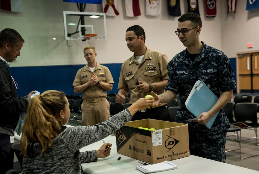 Kayla Day, professional tennis player, hands out autographed tennis balls to Naval Nuclear Power Training Unit students April 4, 2017, at the Bowman Center on Joint Base Charleston - Weapons Station, South Carolina. Day toured the NNPTU campus and signed autographs for Team Charleston members while she was in the Charleston area to compete in the Volvo Car Open tennis tournament.