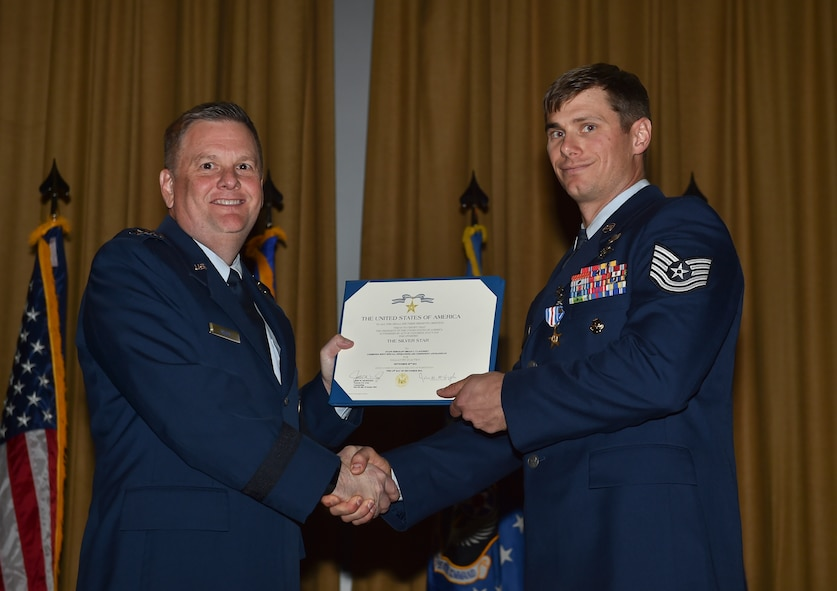 Lt. Gen. Brad Webb, commander of Air Force Special Operations Command, presents Tech. Sgt. Brian Claughsey, a combat controller with the 21st Special Tactics Squadron, a Silver Star Medal, April 7, 2017, at Pope Army Airfield, N.C. Following a 96-hour battle with Taliban forces in Afghanistan, Claughsey was credited with coordinating 17 close air engagements, resulting in 47 enemy killed in action without a single civilian or friendly casualty. (U.S. Air Force photo by Senior Airman Ryan Conroy)