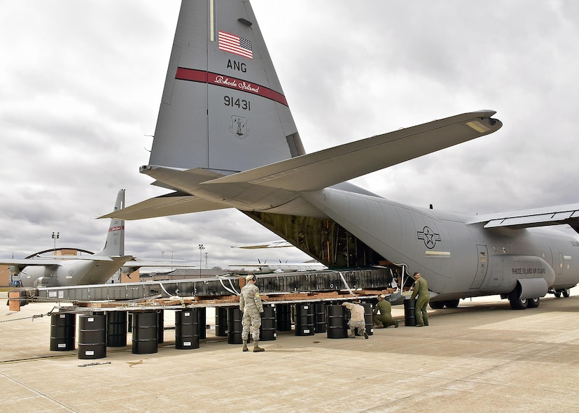 Airmen from the 143d Airlift Wing's Maintenance Group, Operations Group and Logistics Readiness Squadron work together to plan and complete the offload of a detached C-130 wing from the back of a C-130J using the Combat Offload Method B technique. The wing was secured to be used for training by Fuel Cell Airmen, Safety, and Fire personnel.