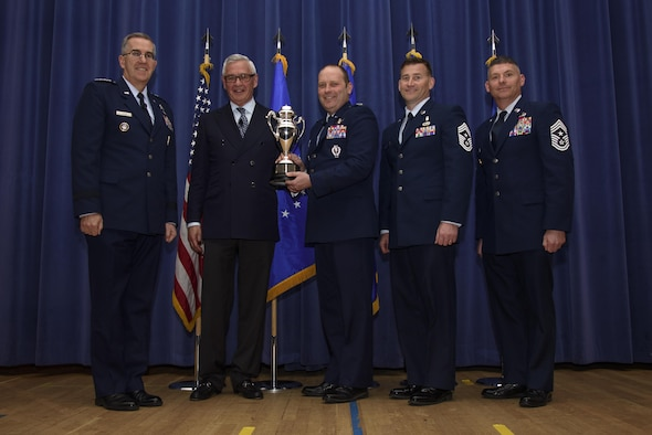 PETERSON AIR FORCE BASE, Colo. –Col. Doug Schiess, 21st Space Wing commander, accepts the Omaha Trophy from Gen. John Hyten, U.S. Strategic Command commander, and Mogens Bay, Strategic Command Consultation Committee, on behalf of the 21st SW during a ceremony in the auditorium on Peterson Air Force Base, Colo., April 6, 2017. This was the first time the 21st SW received the award since its inception in 2008. (U.S. Air Force photo by Airman 1st Class Dennis Hoffman)