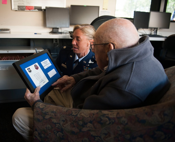 Lt. Col. Allison Black, commander of the 319th Special Operation Squadron, shows retired Lt. Col. Richard E. Cole a framed invitation after a building renaming and dedication ceremony at Hurlburt Field, Fla., April 7, 2017. Cole is the last surviving Doolittle Raider whose Air Force roots date back to the origination of the 319th SOS. (U.S. Air Force photo by Senior Airman Krystal M. Garrett)