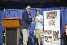 Jimmy Waddle, U.S. Army Corps of Engineers Nashville District Engineering and Construction Division chief, presents an award to Carson Fisher, 7th grade student from Robert E. Ellis Middle School in Hendersonville, Tenn., during the Science, Technology, Engineering and Mathematics Expo at Tennessee State University Gentry Center April 6, 2017.   He was presented with a glass trophy and certificate for his project, a self-rising levee system.