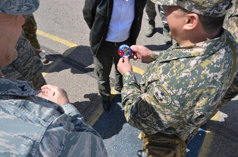 Air Force Col. Troy Daniels (left), vice commander of the 161st Air Refueling Wing, gives a unit patch to a military officer from the Republic of Kazakhstan as a memento, March 31. The wing hosted a Kazakh delegation visit to exchange ideas on emergency management. Kazakhstan and Arizona have been partners in the National Guard's State Partnership Program since 1993. (U.S. Air National Guard photo by 2nd Lt. Tinashe Machona).