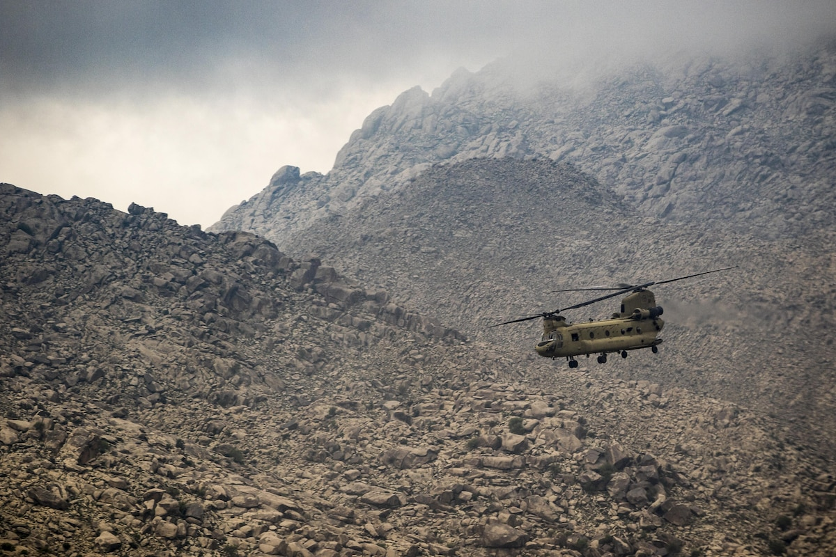 Army helicopter pilots fly over rocky mountains.