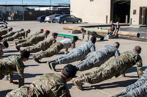 """Members of the 350th Battlefield Airmen Training Squadron and from throughout Joint Base San Antonio-Lackland perform """"memorial push-ups"""" during a memorial remembrance ceremony honoring Lt. Col. William """"Bill"""" Schroeder while his two sons observe April 7, 2017, at JBSA-Lackland, Texas, Medina Annex. Schroeder's unit honored his legacy renaming a drop zone as Schroeder DZ and participated in a """"Monster Mash"""" fitness competition, remembrance ceremony and log march. On April 8, 2016, Schroeder recognized a perilous situation developing and reacted swiftly by putting himself between an armed individual and his first sergeant. In the process, he saved lives of other squadron members while being fatally wounded. Schroeder was posthumously awarded the Airman's Medal, given to those that distinguish themselves by a heroic act – usually at the volunteer risk of their lives but not involving combat. (U.S. Air Force photo by Johnny Saldivar)"""