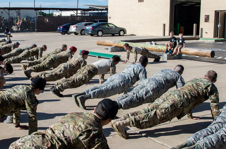 """Members of the 350th Battlefield Airmen Training Squadron and from throughout Joint Base San Antonio-Lackland perform """"memorial push-ups"""" during a memorial remembrance ceremony honoring Lt. Col. William """"Bill"""" Schroeder while his two sons observe April 7, 2017, at JBSA-Lackland, Texas, Medina Annex. Schroeder's unit honored his legacy renaming a drop zone as Schroeder DZ and participated in a """"Monster Mash"""" fitness competition, remembrance ceremony and log march. April 8, 2016, Schroeder recognized a perilous situation developing and reacted swiftly by putting himself between an armed individual and his first sergeant. In the process, he saved lives of other squadron members while being fatally wounded. Schroeder was posthumously awarded the Airman's Medal, given to those that distinguish themselves by a heroic act – usually at the volunteer risk of their lives but not involving combat. (U.S. Air Force photo by Johnny Saldivar)"""