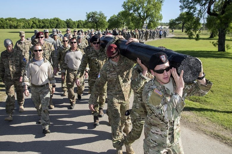 """Members of the 350th Battlefield Airmen Training Squadron and from throughout Joint Base San Antonio-Lackland participated in a 1-mile log march during a memorial remembrance ceremony honoring Lt. Col. William """"Bill"""" Schroeder April 7, 2017, at JBSA-Lackland, Texas, Medina Annex. Schroeder's unit honored his legacy renaming a drop zone as Schroeder DZ and participated in a """"Monster Mash"""" fitness competition, remembrance ceremony and log march. April 8, 2016, Schroeder recognized a perilous situation developing and reacted swiftly by putting himself between an armed individual and his first sergeant. In the process, he saved lives of other squadron members while being fatally wounded. Schroeder was posthumously awarded the Airman's Medal, given to those that distinguish themselves by a heroic act – usually at the volunteer risk of their lives but not involving combat. (U.S. Air Force photo by Johnny Saldivar)"""