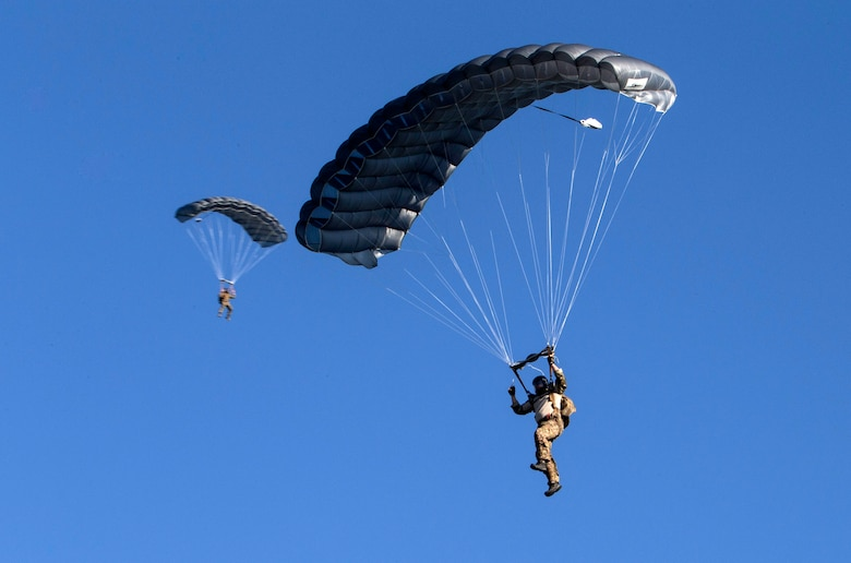 """Members of the 350th Battlefield Airmen Training Squadron prepare to land on the newly renamed Schroeder drop zone during a memorial remembrance ceremony honoring Lt. Col. William """"Bill"""" Schroeder April 7, 2017, at JBSA-Lackland, Texas, Medina Annex. Schroeder's unit honored his legacy renaming a drop zone as Schroeder DZ and participated in a """"Monster Mash"""" fitness competition, remembrance ceremony and log march. On April 8, 2016 Schroeder recognized a perilous situation developing and reacted swiftly by putting himself between an armed individual and his first sergeant. In the process, he saved lives of other squadron members while being fatally wounded. Schroeder was posthumously awarded the Airman's Medal, given to those that distinguish themselves by a heroic act – usually at the volunteer risk of their lives but not involving combat.  (U.S. Air Force photo by Johnny Saldivar)"""
