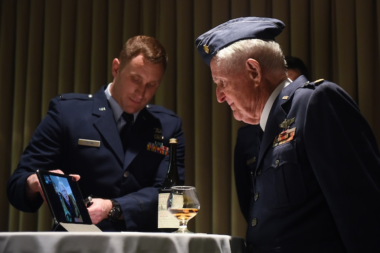 Maj. M. Eugene Johns and Col. Ralph Jenkins, WWII combat aviators and retired Air Force officers with the 510th Fighter Squadron, share a live-streamed greeting during a ceremony to toast their fallen Squadron members, Apr. 7, 2017, at Vandenberg Air Force Base, Calif. Personnel with the 510th FS made a pact that the last two surviving members of the unit who flew combat missions during WWII – Johns and Jenkins – would make a toast from two bottles of brandy which had been saved for the occasion. (U.S. Air Force photo by Michael Peterson/Released)