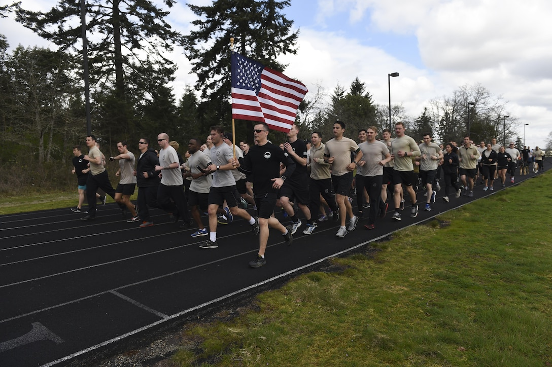 More than 200 members of the 1st Air Support Operations Group, 194th ASOG, 62nd Airlift Wing and Joint Base Lewis- McChord, Wash., both military and civilian, run their last lap of the Tactical Air Control Party 24-hour memorial run at Joint Base Lewis-McChord, Wash., on March 31, 2017. In total they raised approximately $6,000 dollars towards the TACP-Association that has given more than $200K back to the community and their families. (Air Force Photo/ Staff Sgt. Naomi Shipley)