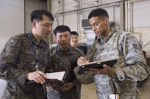 U.S. Air Force Staff Sgt. Robin McClain, a cyber technician assigned to the 621st Contingency Response Wing stationed at Joint Base McGuire-Dix-Lakehurst, N.J., talks about procedures with two Republic of Korea Air Force Airmen during exercise Turbo Distribution 17-3 at Pohang Air Base, Republic of Korea, April 7, 2017. The CRW specializes in rapidly establishing hubs for cargo distribution operations worldwide, to include remote and austere locations, on short notice. (U.S. Air Force photo by Tech. Sgt. Gustavo Gonzalez/RELEASED)