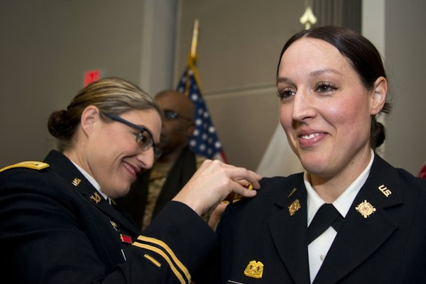 Iowa Army National Guard Maj. Jill Finkel, left, pins a new gold leaf rank insignia on Massachusetts Army National Guard Maj. Molly Alesch during her promotion ceremony at Hanscom Air Force Base, Mass., March 17, 2017. Finkel and Alesch are sisters and their youngest sister, Army Spc. Kristen Alesch, who serves in the Tennessee National Guard, also attended the promotion ceremony. Massachusetts Army National Guard photo by Sgt. 1st Class Whitney Hughes