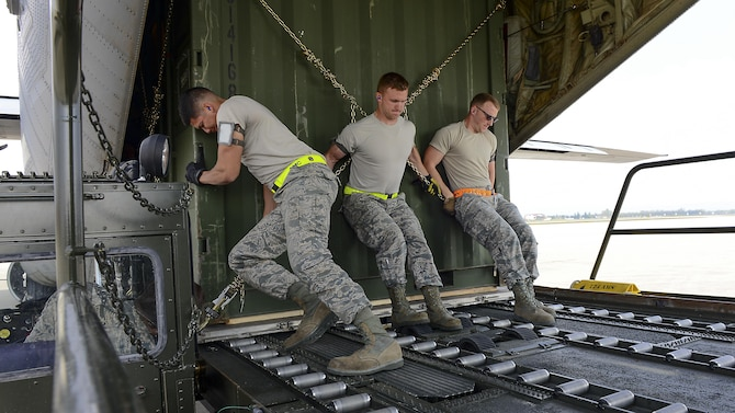 Senior Airman Daniel Zamora, Airman Skylar Keyes and Senior Airman Timothy Flowers, 724th Air Mobility Squadron passenger service agents, push a shipping crate onto a C-130 Hercules at Aviano Air Base, Italy, April 6, 2017.  Airmen from the 724th AMS support more than 500 airlift missions a year.  (U.S. Air Force photo by Airman 1st Class Ryan Brooks)