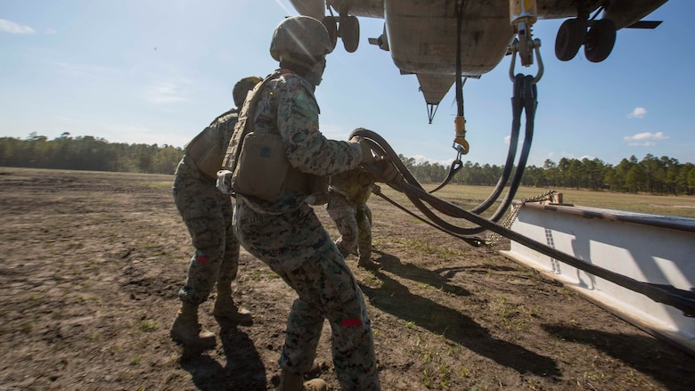 Marines attach a 1,000 pound metal beam to a CH-53E Super Stallion while conducting helicopter support team operations at Marine Corps Base Camp Lejeune, N.C., March 30, 2017. The training helped the Marines hone their skills in the transportation of gear via air assets and was part of field exercise Bold Bronco 17. The Marines are landing support specialists with 2nd Transportation Support Battalion, 2nd Marine Logistics Group.