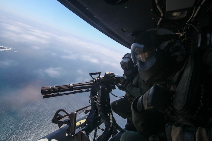 Sgt. George Hamil, an aerial observer, and Sgt. Zachary Zimberg, a crewcheif with Marine Medium Tiltrotor Squadron 161, 15th Marine Expeditionary Unit, uses direct fire to assault targets on the objective during Amphibious Squadron-Marine Expeditionary Unit Integration, April 5, 2017. Hamil manned the GAU-17/A minigun and Zimberg provided oversight aboard a UH-1Y Huey. PMINT is a vital exercise used to hone skills and tactics in order to enhance the MEU's operational abilities to be flexible and responsive.