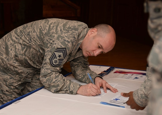 U.S. Air Force Chief Master Sgt. Curtis Stanley, 100th Air Refueling Wing command chief, fills out the first donation from RAF Mildenhall to the Air Force Assistance Fund for the fiscal year April 7, 2017, on RAF Mildenhall, England. The AFAF is an annual effort to raise funds for the charitable affiliates that provide support to Air Force active duty-members, retirees, reservists, guard and their dependents when needed. (U.S. Air Force Photo by Airman 1st Class Tenley Long)