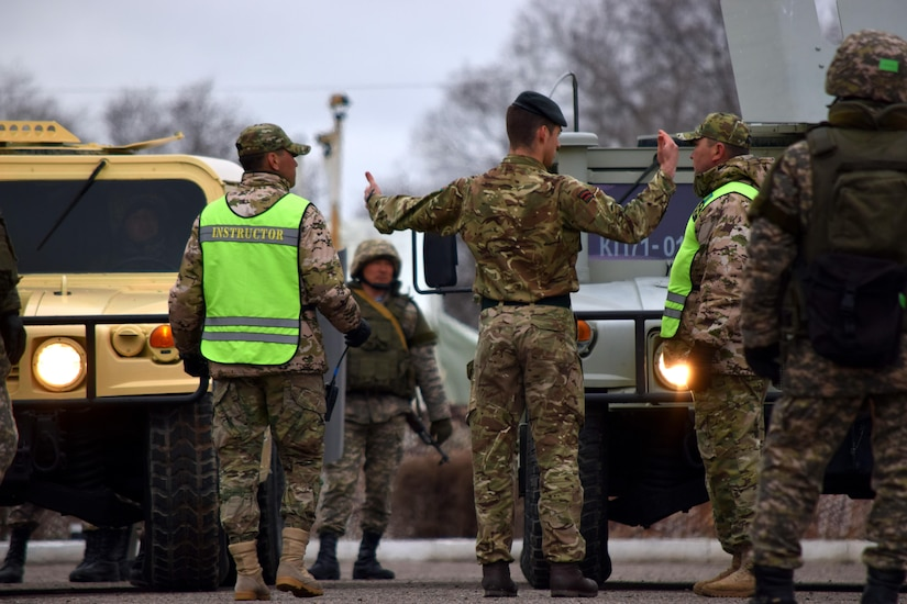 A U.K. Soldier with the British Army's 1st Battalion, The Rifles, 160 Brigade, discusses options for using vehicles during crowd control with a Kazakhstani instructor from the Kazakhstan Peacekeeping Battalion during Steppe Eagle Koktem, Apr. 3, 2017, at Illisky Training Center, Kazakhstan.