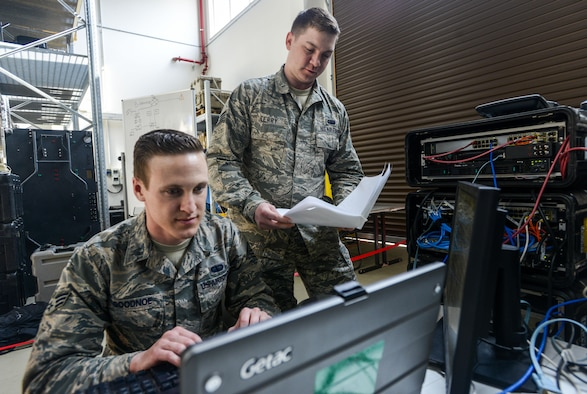 U.S. Air Force Senior Airman Thomas Goodnoe, left, 1st Combat Communications Squadron tactical network operations technician, and Staff Sgt. Darryl Terry, right, 1st CBCS cyber transport supervisor, review their systems against their technical guides during cyber security audit March 16, 2017, on Ramstein Air Base, Germany. The U.S. Army Cyber Protection Brigade's 201st Cyber Protection Team audited the 1st CBCS' deployable network control centers, which are tactical communications kits that allow 1st CBCS operators to set up and manage secure communications in deployed locations. (U.S. Air Force photo/Staff Sgt. Timothy Moore)