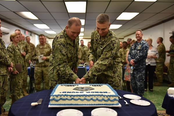 Navy Rear Adm. Peter J. Clarke, outgoing commander for Joint Task Force Guantanamo, and Navy Rear Adm. Edward B. Cashman, the incoming commander, celebrate the change of command ceremony by cutting the cake together April 7, 2017 here at the Naval Station Chapel. Clarke commanded the JTF GTMO from November 2015 to April 2017.