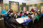 PSNS & IMF Science, Technology, Engineering, and Math Outreach Coordinator Corinne Beach shows students from Pinecrest Elementary School how to use a battery to demonstrate electrical circuitry during a Navy STEM event at the Puget Sound Navy Museum, March 17, 2017, in Bremerton, Washington. Volunteers from PSNS & IMF teamed up with Puget Sound Navy Museum staff to hold a two-day STEM outreach event for local students at the museum March 16-17. (U.S. Navy photo by Zachary Frank, PSNS & IMF photographer)