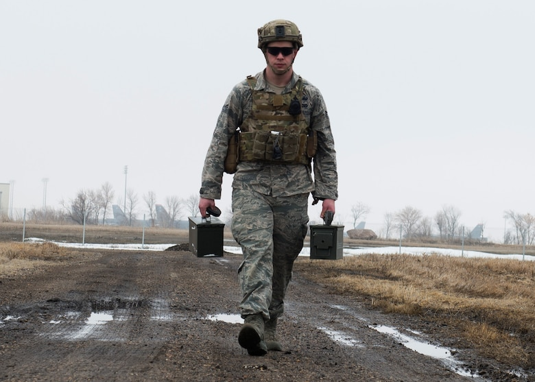 Senior Airman Adam Allen, 5th Civil Engineer Squadron explosive ordnance disposal team leader, carries ammunition cans at Minot Air Force Base, N.D., March 28, 2017. During training, EOD Airmen practiced safely securing inert unexploded ordnance parts to ensure the safety of personnel transporting a UXO. (U.S. Air Force photo/Airman 1st Class Alyssa M. Akers)