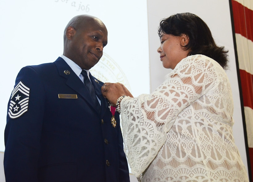 Cheryl Tubbs, wife of Chief Master Sgt Lyndon Tubbs, Command Chief of the 94th Airlift Wing, Dobbins Air Reserve Base, Ga., pins on the retirement pin during his retirement ceremony, honoring a 33 year career on Dobbins April 1, 2012. (U.S. Air Force photo/Don Peek)
