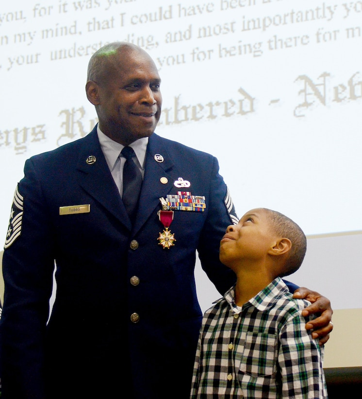 Evan Tubbs, son of Chief Master Sgt Lyndon Tubbs, 94th Airlift Wing, command chief, stands by his dad as he prepares to receive the Childs Medal during Tubbs retirement ceremony held on Dobbins Air Reserve Base, Ga., April 2, 2017, where he was honored for a 33 year successful career. (U.S. Air Force photo/Don Peek)