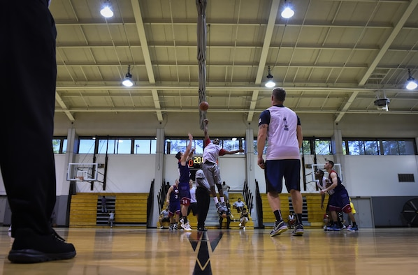 Members of the 1st Special Operations Medical Group and 1st Special Operations Civil Engineer Squadron basketball teams contest for the tip-off to start the intramural basketball championship at the Aderholt Fitness Center on Hurlburt Field, Fla., April 6, 2017. For eight weeks, 12 teams competed through a single-elimination tournament to qualify for the championship game. (U.S. Air Force photo by Airman 1st Class Joseph Pick)