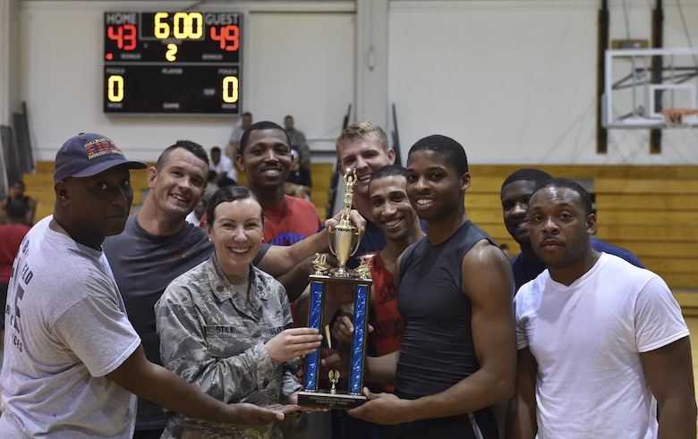 The 1st Special Operations Civil Engineer Squadron basketball team celebrate with the first place trophy after the intramural basketball championship at the Aderholt Fitness Center on Hurlburt Field, Fla., April 6, 2017. The 1st SOCES bested the 1st Special Operations Medical Group by the score of 49 to 43. (U.S. Air Force photo by Airman 1st Class Joseph Pick)