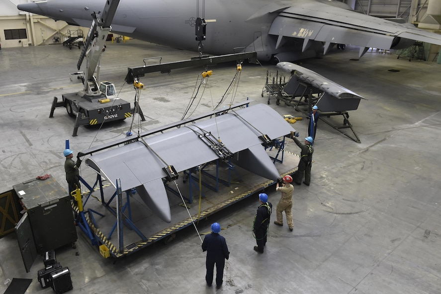 Airmen and civilians from the 62nd Maintenance Squadron hoist a C-17 Globemaster III flap from a stand April 6, 2017, at Joint Base Lewis-McChord, Wash. The 2,200 pound flap replaced a faulty flap and is the first flap change to ever be completed at McChord Field. (U.S. Air Force photo/Tech. Sgt. Tim Chacon)