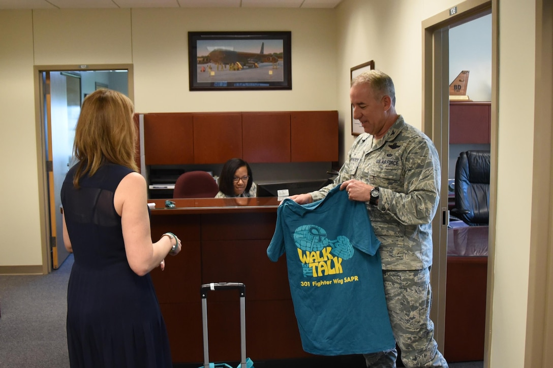 Ms. Laura Loftin, 301st Fighter Wing sexual assault response coordinator, hands out teal t-shirts to Tenth Air Force staff members in order to raise awareness of sexual assault and to empower members to take action in order