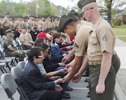 Marines hand ceremonial purple heart pins to family of fallen Marines with 2nd Light Armored Reconnaissance Battalion, 2nd Marine Division during a memorial ceremony at Camp Lejeune, N.C., April 7, 2017. The ceremony honored fallen Marines as well as families and friends of the 2nd LAR community. (U.S. Marine Corps photo by Lance Cpl. Raul Torres)