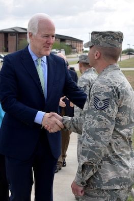 Sen. John Cornyn III, Senate Majority Whip for the 115th Congress, meets U.S. Air Force Tech. Sgt. Aaron Dvorak, 315th Training Squadron geospatial intelligence analysis course chief, before his press conference at the RQ-1 Predator aircraft display on Goodfellow Air Force Base, Texas, April 10, 2017. Dvorak explained to Cornyn how Goodfellow trains intelligence analysts here and how our training ties to the aircraft. (U.S. Air Force photo by Staff Sgt. Joshua Edwards/Released)